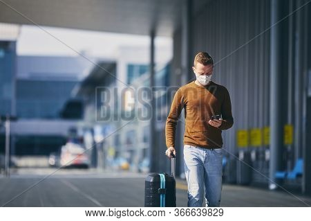 Man Wearing Face Mask And Walking To Airport Terminal. Themes Traveling During Pandemic And Personal