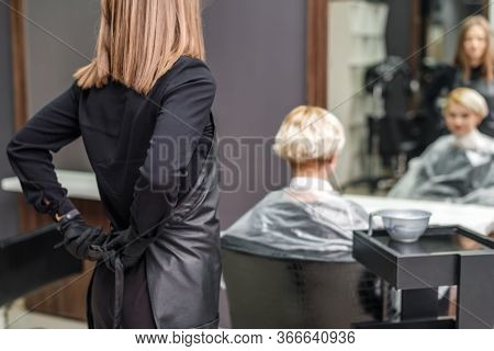 The Professional Female Hairdresser Puts On Black Apron To Dye The Womans Hair In The Hair Salon.