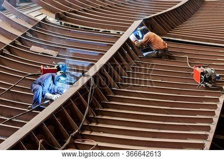 Professional Shipbuilders Working With A Safety Helmet, Welding Parts Of A New Ship's Hull