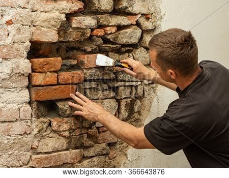 Worker Reconstructing Old Stone Wall. Old House Reconstruction, Repair