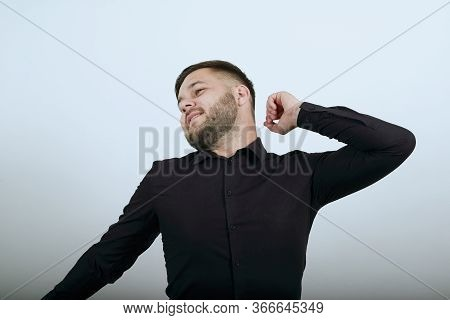 Young Bearded Dark Haired Man In Black Stylish Shirt On White Background, Male Bored, He Stretches H