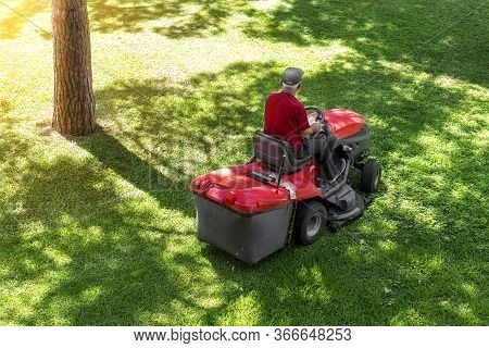 Top Down Above View Of Professional Lawn Mower Worker Cutting Fresh Green Grass With Landcaping Trac
