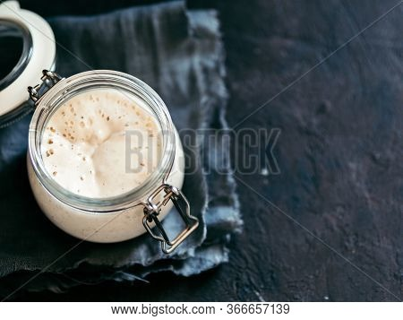 Wheat Sourdough Starter. Glass Jar With Sourdough Starter On Dark Background, Copy Space.