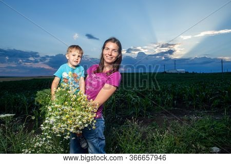woman with toddler outside with wildflowers