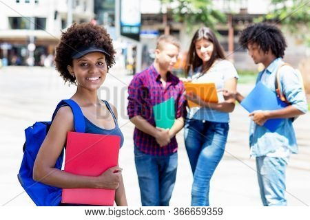 Beautiful Afro American Female Student With Group Of Multi Ethnic Young Adults Outdoor In City In Su