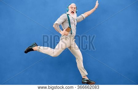 Senior Crazy Man Jumping While Listening Music With Wireless Headphones - Hipster Old Guy Having Fun