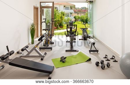 Modern Concept Of Green Nature Eco Style Gym. Front View Of Stylish Training Room Interior In Hotel,