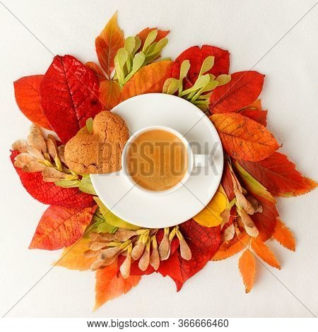Cup Of Coffee And Autumn Leaves Wreath On A White Table, Seasonal Warming Flatlay Concept Of Menu -