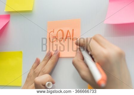 Goal. Business Woman Hand Writing With Colored Sheets Sticky Note Paper On White Board Background In
