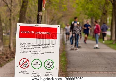 Montreal, Ca - 16 May 2020 : Sign Showing Covid-19 Safety Guidelines As Many People Gather In Laurie