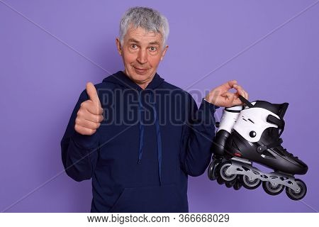 Picture Of Senior Man Wearing Sporty Clothing, Holding Roller Skates, Showing Thumb Up, Being Happy