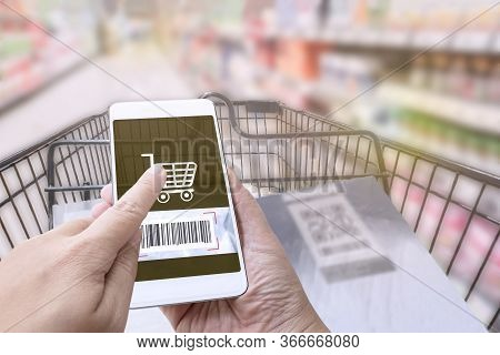 Online Order Grocery Shopping On Touch Screen Concept. Woman Hand Holding Smart Phone And Scanning B