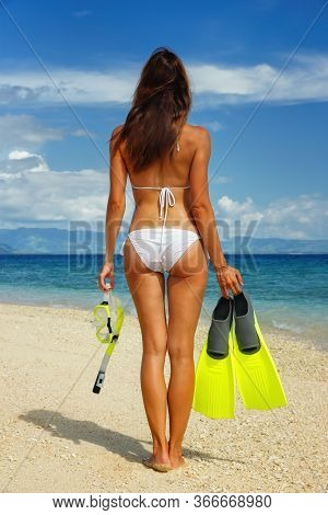 Young Woman In Bikini Standing On A Beach With Mask, Snorkel And Fins