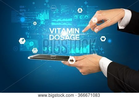 Close-up of a touchscreen with VITAMIN DOSAGE inscription, medical concept