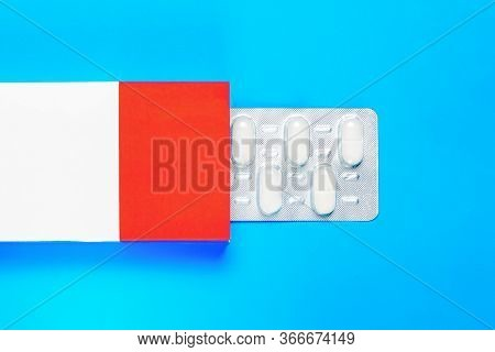 Blister Pack With Pills In A Red-white Box On A Blue Background. Copy Space. Flat Lay