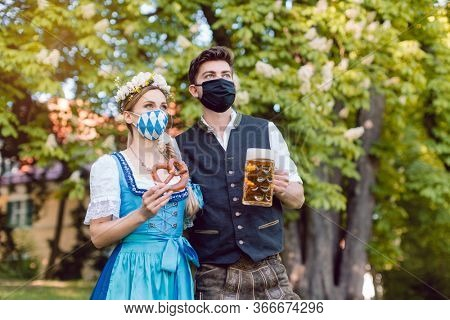Bavarian couple during the coronavirus crisis with beer and pretzel