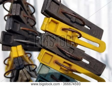 Metal And Plastic Clothespins In Yellow, Green And Gray, On A Clothesline, With Traces Of Rust. In T