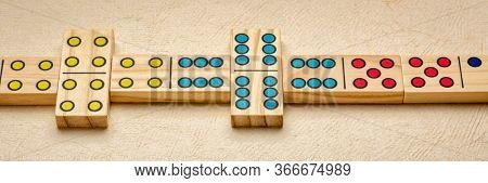 row of wooden domino pieces with colorful pips (dots), panoramic web banner