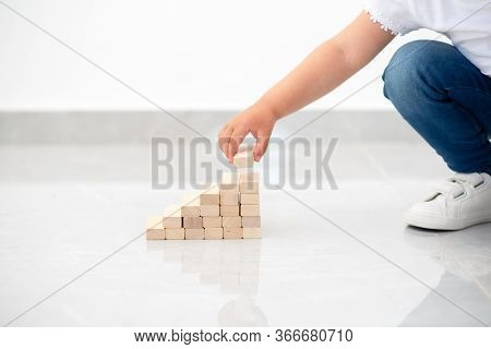 Close Up Child Hand Arranging Wood Block Stacking As Step Stair. Instilling Leadership Skills In Chi