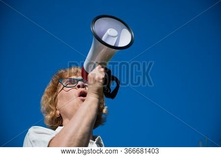 Emotional Senior Woman Makes A Speech In A Megaphone On The Outside. A Pensioner Yells Into A Sound
