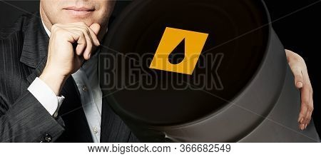 Man Holding Crude Oil Barrel On Black Background. Crude Oil And Petroleum Industry Concept