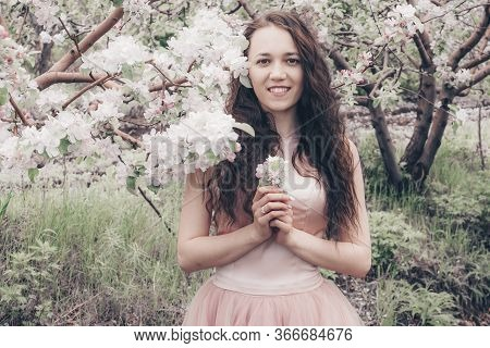 Photoshoot In The Colors Of The Apple Tree. Portrait Of A Beautiful Girl In The Apple Orchard. Flowe
