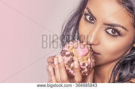 Beautiful woman holding chocolate cup cake temptingly to her mouth,