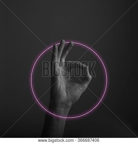 Close Up Of An Okay Hand Gesture With Abstract Neon Light Glow. Ok Hand Sign