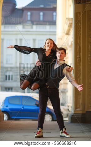 Young Couple Guy And Girl Dancing Together On The Street Of A European Town