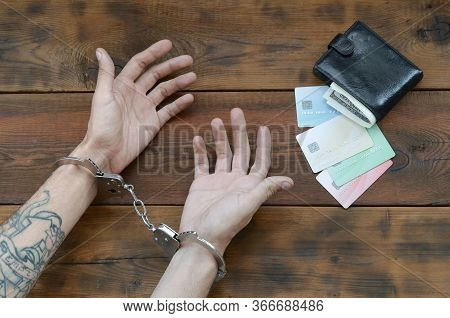 Cuffed Hands Of Tattooed Criminal Suspect Of Carding And Fake Credit Cards With Cash In Purse As Evi