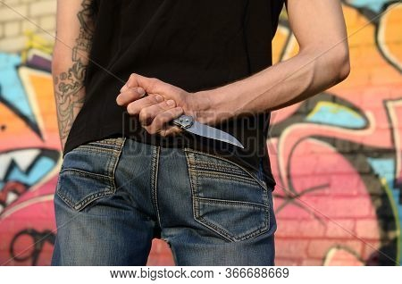 Back View Of Young Caucasian Man With Knife In His Hand Against Ghetto Brick Wall With Graffiti Pain