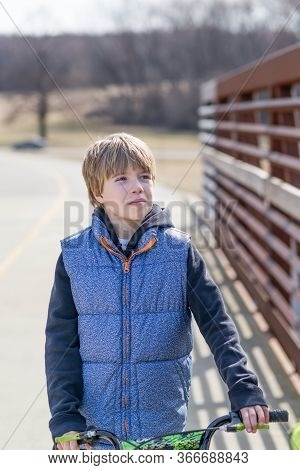 Portrait Of A Child On A Bicycle On  Sunny Day
