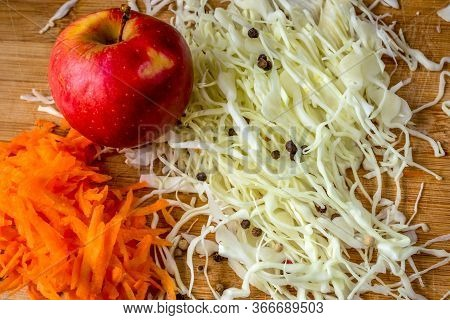Slices Of Cabbage And Carrots, Red Apple And Spices Are The Ingredients For A Fresh Salad Or Marinad