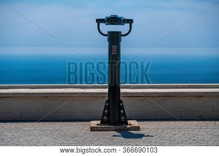 Coin Operated Binoculars And Blue Sea Background. Public Panoramic Binoculars To Observe The Sea Vie