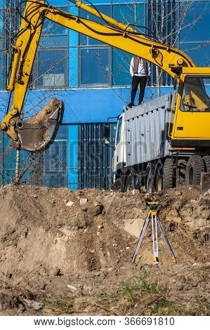 Excavator Loader, Dump Truck And Geodetic Device During Excavation Work At A Construction Site. Load