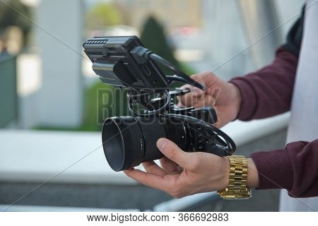 Man Holding Gimbal Stabilizer Outdoor. Gimbal Operator With Black Equipament - Stabilizer And Camera