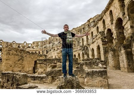 El Jam.tunisia.may 21, 2013.a Male Tourist Poses Against The Backdrop Of The Roman Amphitheater In T