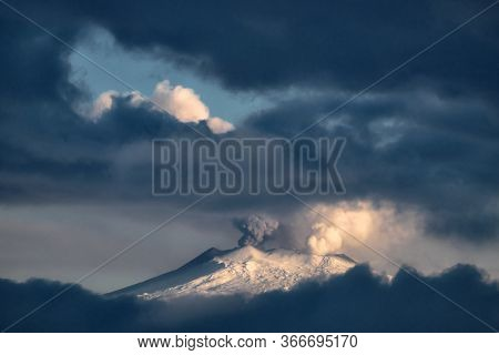 snow covered Etna Mountain emit smoke from central crater framed by stormy low clouds; the volcano is a natural landmark of Sicily