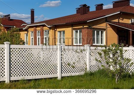 White Plastic Fence Around A House In A Cottage Village. Concept Of Landscaping, Protection, Fencing