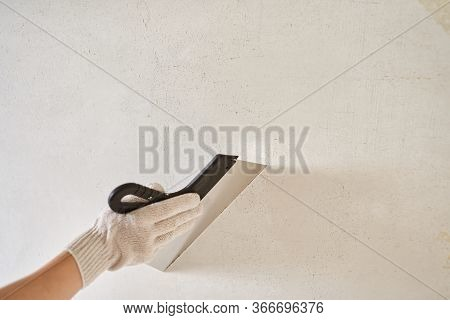 Spatula With Putty In Hand With A Glove Against A Light Wall. Worker Puts Of Plaster On Wall. Repair