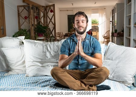 Handsome Man With Blue Shirt, Practicing Meditation Or Yoga In The Cross-legged Posture, On The Sofa