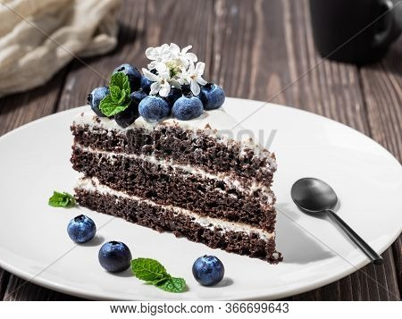 Slice Of Homemade Bird Cherry Cake With Sour Cream, Decorated With Blueberries And Mint Leaves On A