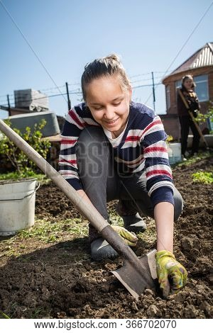 Teen Girl Dig A Garden Near A Country House. Spring Preparation For Planting Harvest Concept. Help F