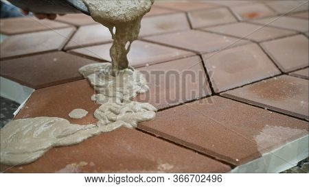 Filling Paving Slabs With A Solution On The Street. The Builder Fills The Seams Between The Paving S