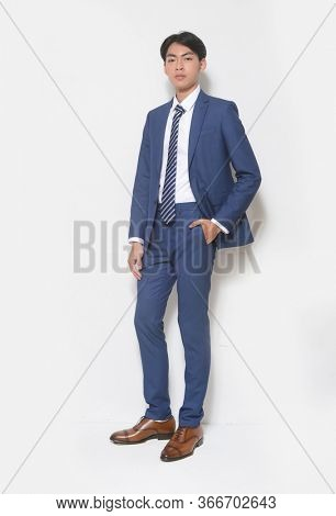 Men's beauty, fashion. Handsome full body young businessman wearing blue suit and blue striped tie with hands holds pockets standing on white background,