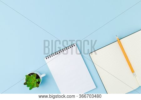 Spiral Notebook With Open Notepad A Pencil And A Plant On Blue Isolated Background. Design Concept W