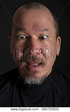 Portrait Of A Mixed Race Man With A Beard And A Surprised Expression, On Black Background