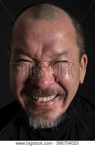 Portrait Of A Mixed Race Man With A Beard And A Sneaky Smile On His Face, On Black Background