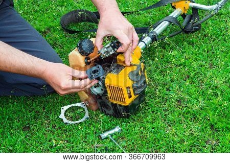Worker Repairs Carburetor In Trimmer Or Lawn Mower That Lies On The Grass