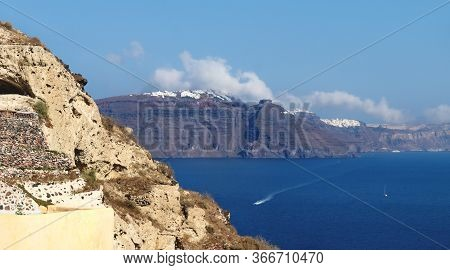 High Volcanic Cliffs Along The Coastline With Blue Ocean And White Clouds Over The Village Of Fira W